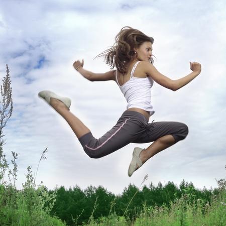 beauty girl jumping on green grass photo