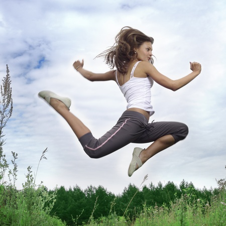 woman exercising: beauty girl jumping on green grass Stock Photo