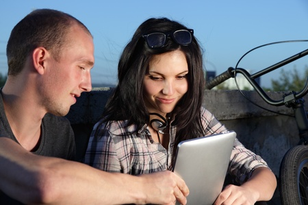 beauty girl and boy with laptop pc outdoors photo