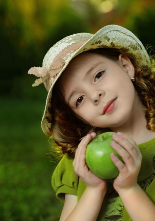 child food: girl with fruit in park