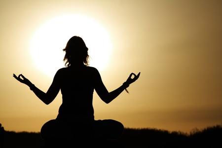 joga: beauty girl in lotus pose on sunrise beach