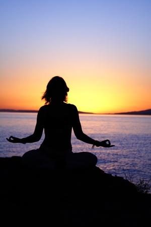 beauty girl in lotus pose on sunrise beach photo