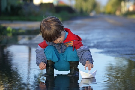 a little boy playing paper ship on a puddle of water photo