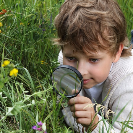 78: boy with magnifying glass outdoors Stock Photo