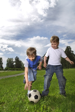 boys only: two happy boys playing soccer in a field