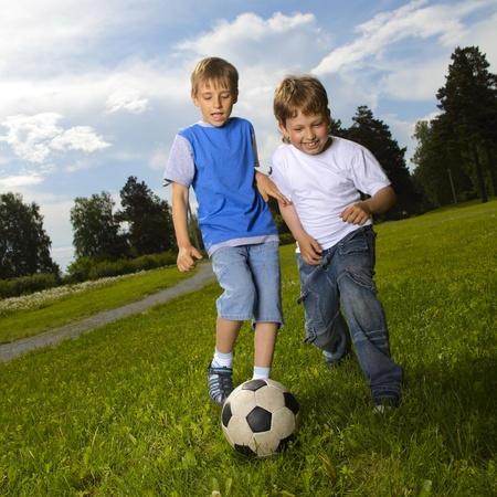 two happy boys playing soccer in the field photo