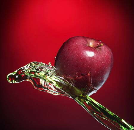red apple in juice stream photo