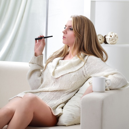 beauty girl indoors with e-cigarette photo