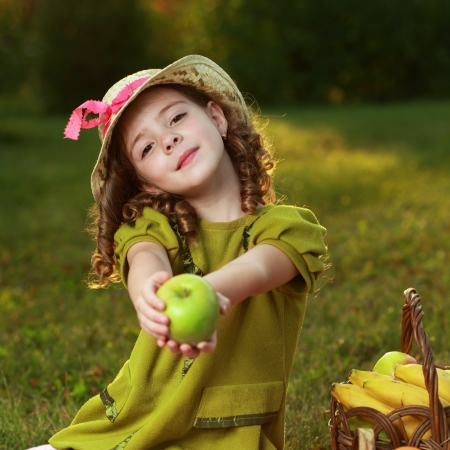 cute baby girl: girl with fruit in park