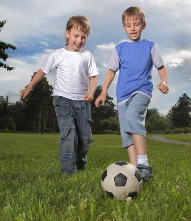 两个快乐的男孩踢足球