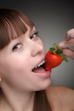 beauty girl eating strawberries photo