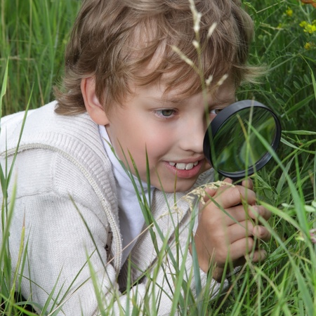 boy with magnifying glass outdoors photo