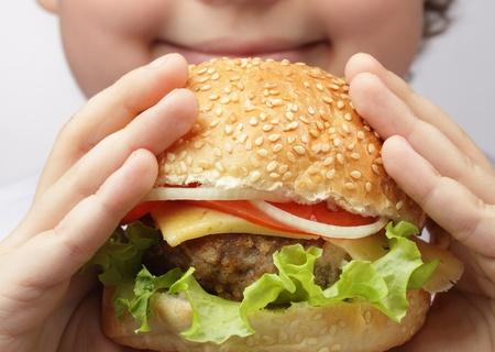 niños comiendo: niño feliz con hamburguesa Foto de archivo