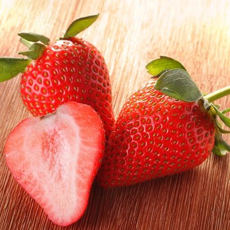 frutillas: tres fresas en la cubierta de madera