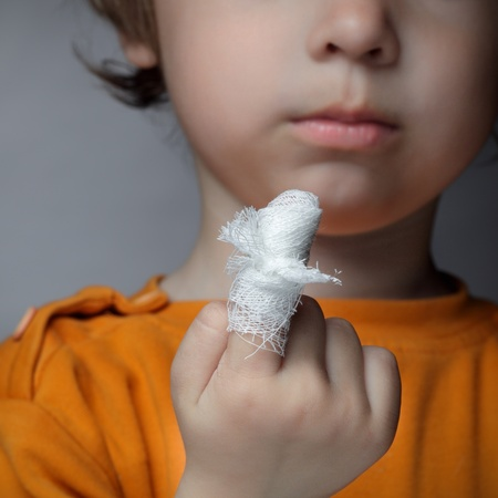 mischief: boy with a wound on his finger Stock Photo