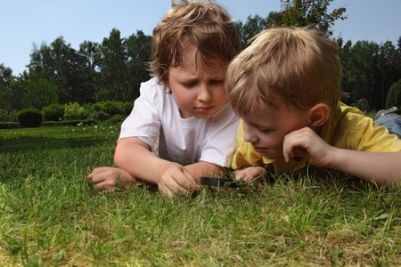 two boys with magnifying glass outdoors photo