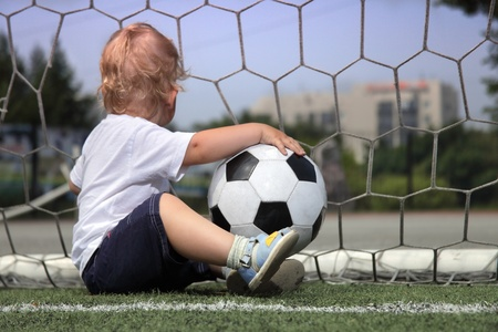 elementary age boys: boy with ball in gate Stock Photo
