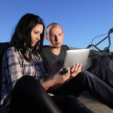 beauty girl and boy with tablet pc outdoors photo