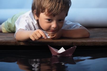 papier schip in kinderen hand