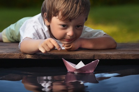 small paper: paper ship in children hand Stock Photo