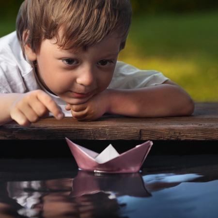 small paper: paper ship in children hand Stock Photo