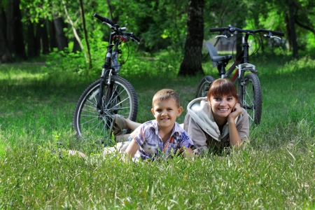 family on bike cycling in park photo