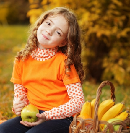cute little girl smiling: girl with fruit in park