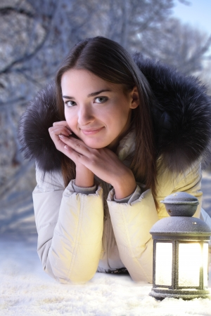 beautiful girl on winter forest with lantern photo