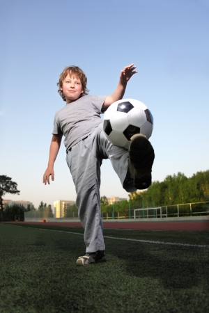 outdoor activities: happy boy play in soccer Stock Photo