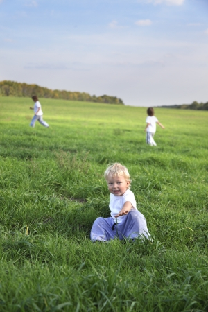 three children run on grass field photo