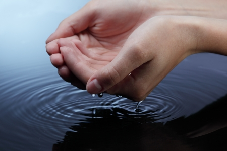 hand wash: woman hands in blue water Stock Photo