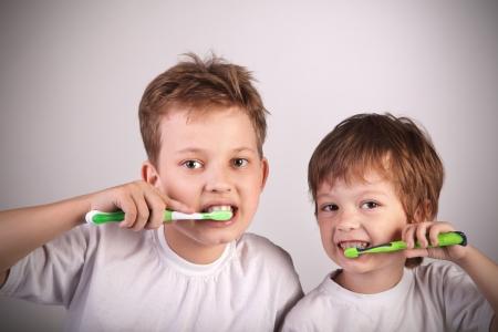 cepillarse los dientes: dos ni�os felices con cepillo de dientes