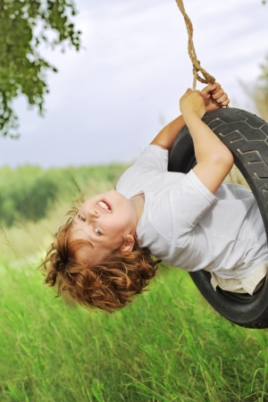 happy boy on swing outdoors Stock Photo