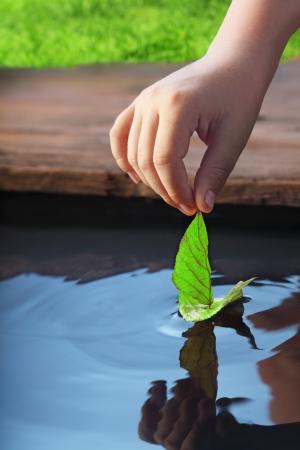 hand water: green leaf-ship in children hand