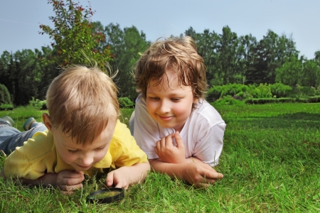 7 8 years: two boys with magnifying glass outdoors