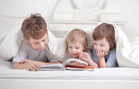 three boy read book indoors photo