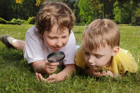 야외에서 돋보기와 두 아들