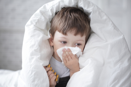 neus: jongen veegt zijn neus met een tissue