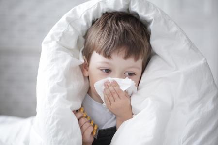 fieber: Junge wischt sich die Nase mit einem Taschentuch