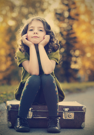 resentful girl on suitcase photo