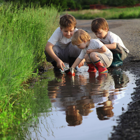 kids playing beach: three boy play in  puddle