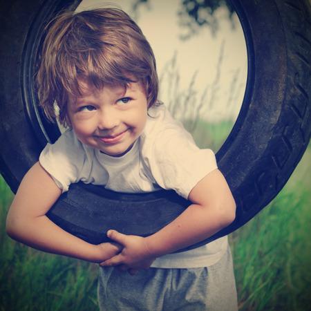 swing: happy boy on swing outdoors Stock Photo