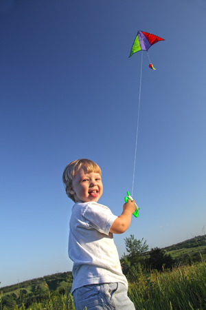 happy kid flies a kite photo