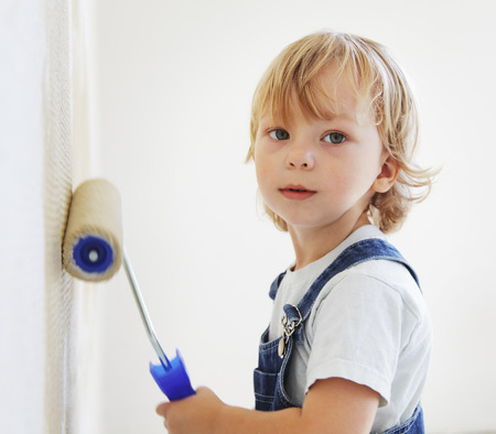 boy paints the wall roller photo