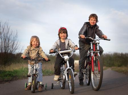 niños en bicicleta: tres hermanos andan en bicicleta
