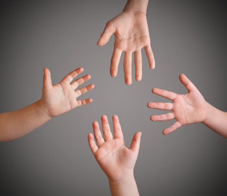 child's: four childrens hands on a gray background Stock Photo