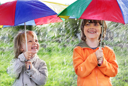 two happy brother with umbrella outdoors photo