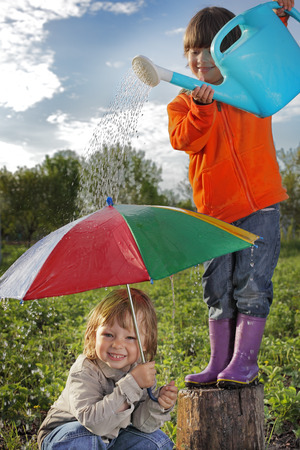 two brothers play in rain outdoors photo