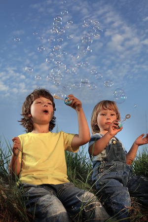 two happy boy blowing bubbles on nature photo