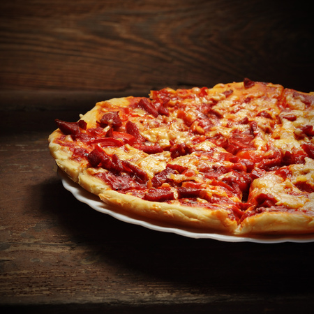 round pizza on wood background photo